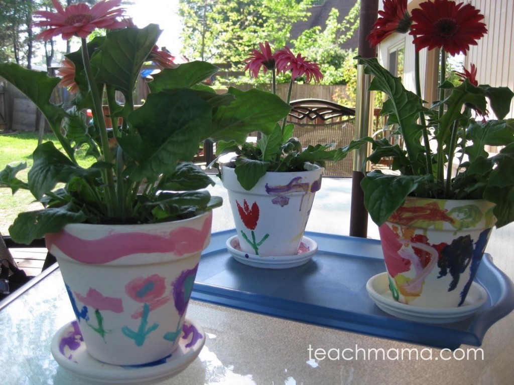 three painted flower pots on patio table