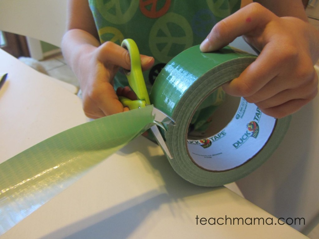 child cutting green duct tape