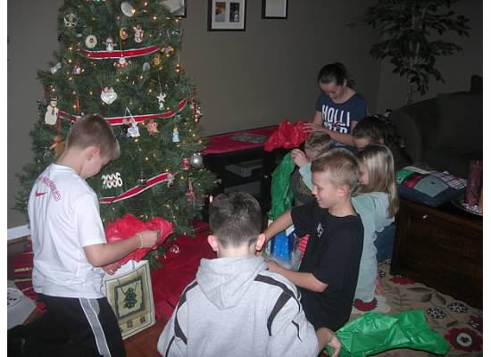 kids opening presents by a tree
