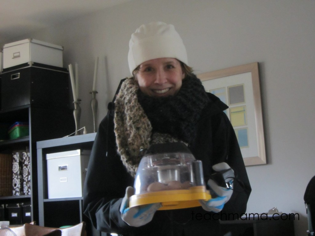 woman with winter hat and scarf holding egg incubator