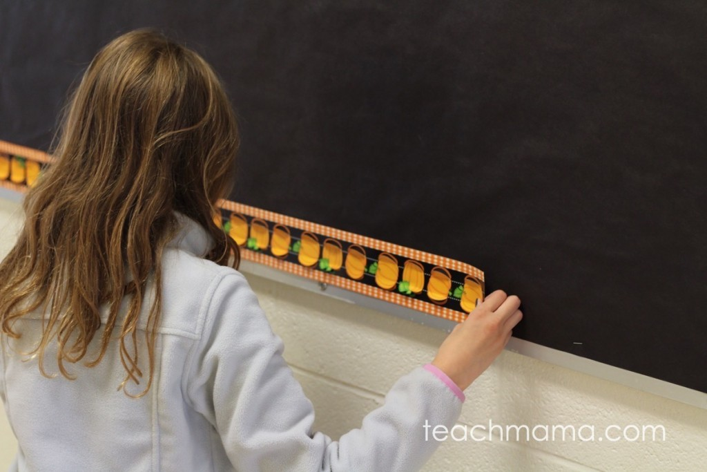 girl putting pumpkin border on bulletin board