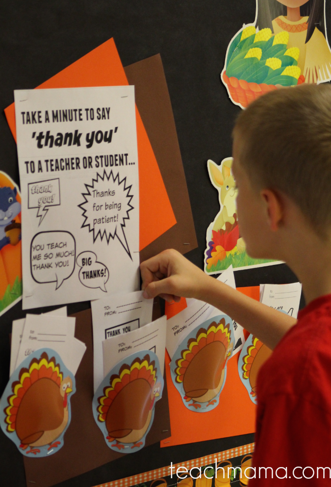 boy putting thankful note on fall bulletin board