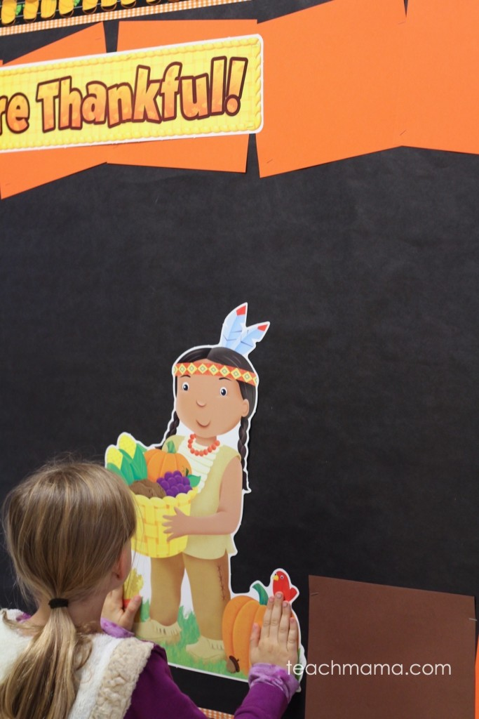 girl puts native american girl on bulletin board