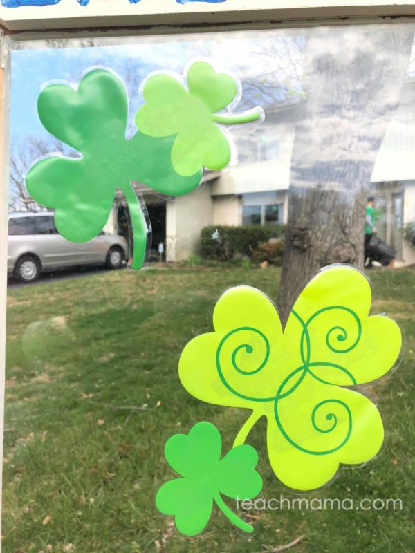 shamrocks on window of little free library in front of someone's house