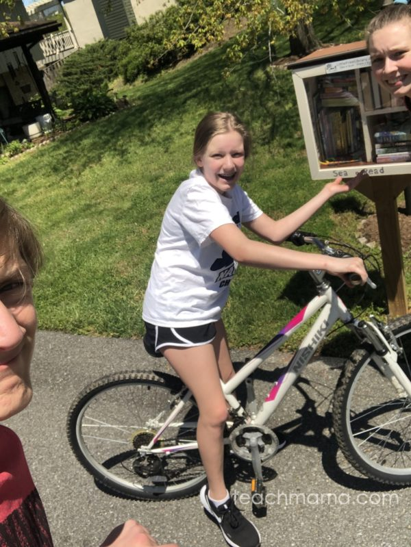 two girls and a boy near a little free library
