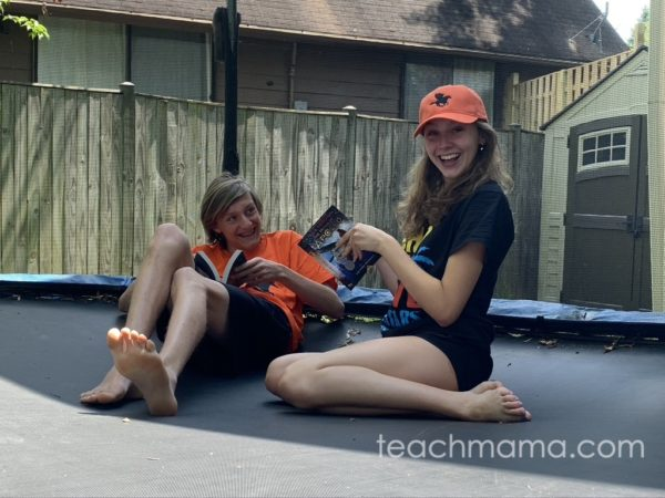 boy and girl reading books on trampoline