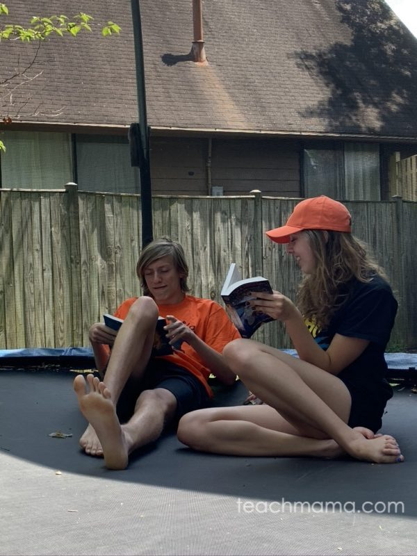two kids reading book on trampoline