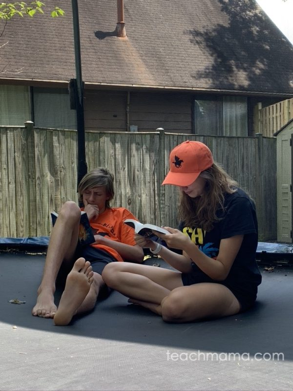 boy and girl reading book on trampoline