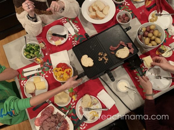 family table full of food and raclette grill